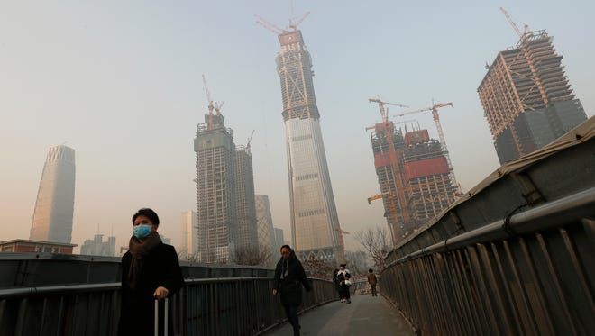 People, some wearing masks for protection against air pollution, walk on a pedestrian overhead bridge in Beijing as the capital of China is shrouded by heavy smog on Dec. 19, 2016.