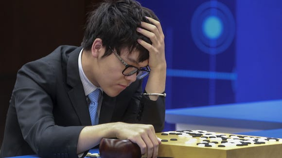 Chinese Go player Ke Jie reacts as he plays a match