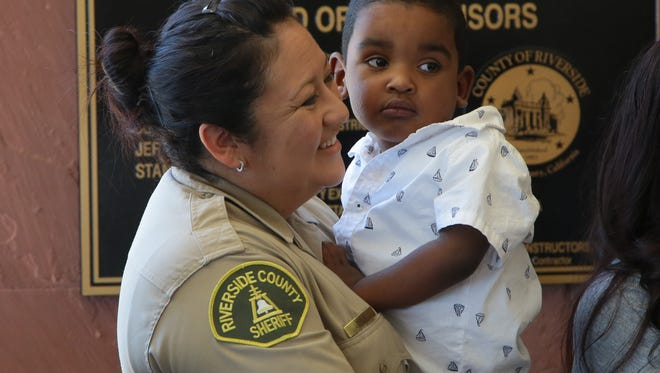 Sheriff's Deputy Alicia Lopez holds Matthew Castleberry, Jr., during a media event at the Riverside County Sheriff's Department in Palm Desert, Calif., Tuesday, July 11, 2017.  Alicia will be donating her kidney to three-year-old Matthew who suffered severe damage to his bladder and kidneys from posterior urethral valves.