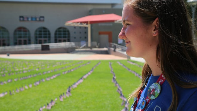 Palm Desert High School senior Maddie Wales looks out at the 2,977 flags she planted on her school's quad to honor those who died in the September 11th attacks, Monday, September 11, 2017.