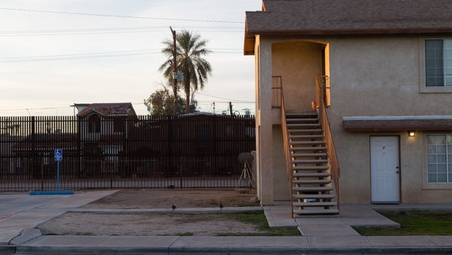 A section of the border wall stands next to homes in Calexico, California. The Trump administration plans to a portion of the wall elsewhere in Calexico.