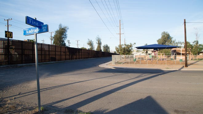 The border fence runs along a street in Calexico, California. On the other side is the larger city of Mexicali.