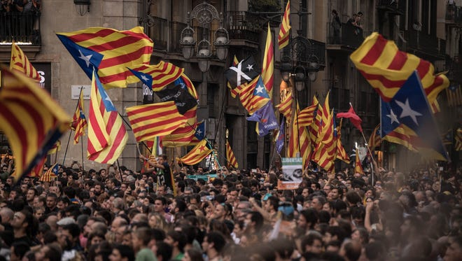 Catalan Independence supporters are pictured outside the Catalan Government building, Palau de la Generalitat, to celebrate their vote of independence from Spain on Friday.