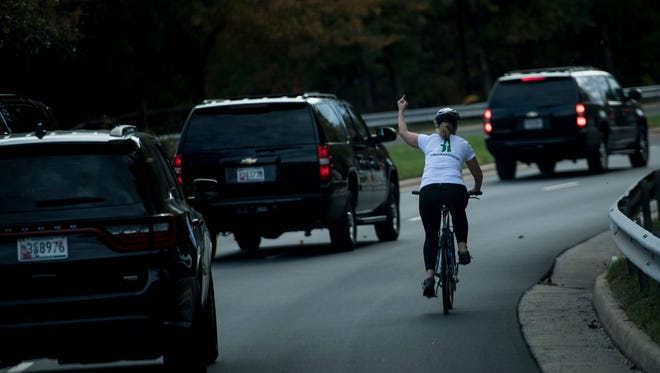 Juli Briskman gestures with her middle finger as a motorcade with US President Donald Trump departs Trump National Golf Course in Virginia on Oct. 28.