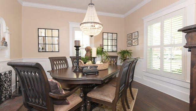 The home's current owners use one of the home's front rooms as a formal dining space.