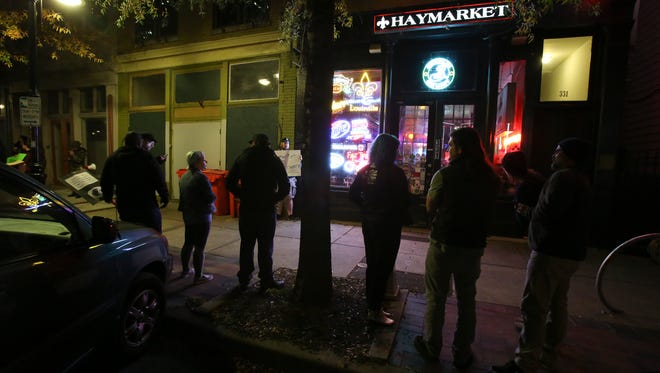 Protesters stand outside Haymarket Whiskey Bar on Nov. 29, 2017, in response to the bar's reopening. The bar closed earlier this month after a woman accused its owner of raping her in a widely shared Facebook post.