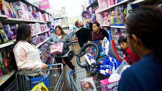Families crowd the toy aisles during the Joy of Giving event Saturday, Dec. 16, 2017, at a Walmart on Collier Boulevard in East Naples. Hundreds of Collier County families were able to spend $100 for each child, starting at 6 a.m.
