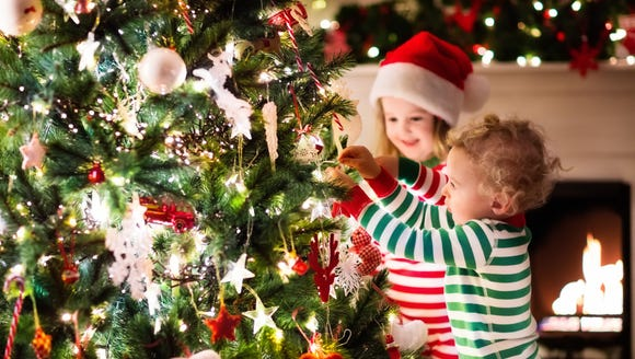 Happy little kids decorate a Christmas treee.