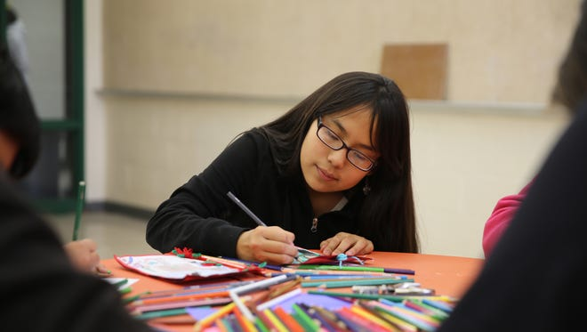Seventh-grader Destiny Lee finishes her drawing on a Christmas card Wednesday that she made in art class at Newcomb Middle School for a resident of the Chinle (Ariz.) Nursing Home.