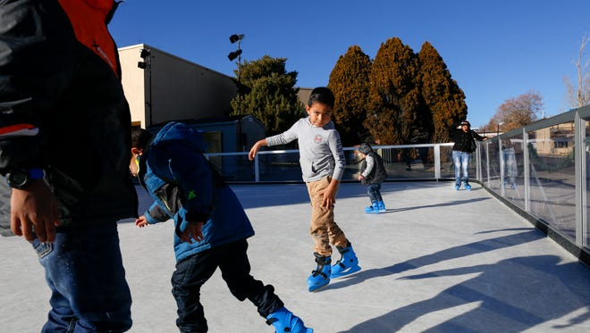 From left, Mathias Benavidez, Ambrosio Gallegos, Manulito Gallegos and Laura Benavidez skate on Dec. 19, 2017, at the Farmington Civic Center's seasonal ice rink.