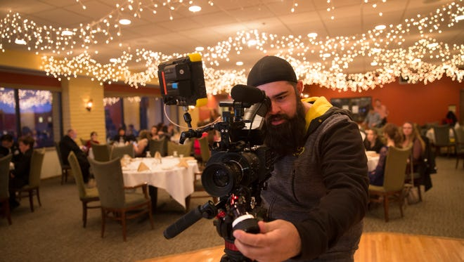 "Director Brent Garcia frames a shot during the filming of ""Aurora's Law"" on Wednesday at the San Juan Country Club in Farmington."