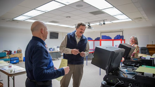 Mark Pavlik, center, casts his ballot during a special election for school levies on Tuesday at the Farmington Municipal School District office.