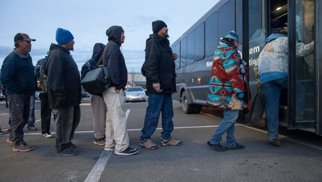 Commuters board a Navajo Transit System bus on Jan. 4 at the Walmart parking lot at 1400 W. Main St. in Farmington.