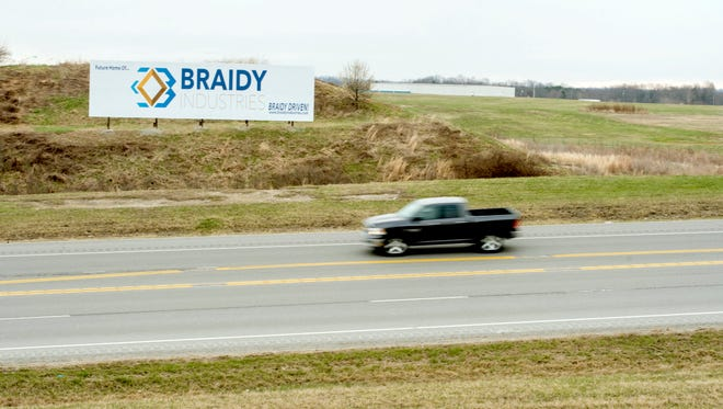 A pickup truck passes by the EastPark Industrial Center Thursday, March 8, 2018, near Ashland, Ky. Braidy Industries plans on building a 2.5 million square-foot aluminum mill on the 204-acre lot at right.
