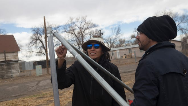 Volunteer Kyle Jim, left and Deion Hayes build a fence on Sunday at the Healing Circle Drop-In Center in Shiprock. The center's greenhouse was vandalized on New Year's Day weekend.