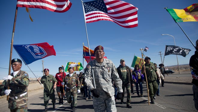 U.S. Army Sgt. Anderson Jim carries the flag while marching with veterans along U.S. Highway 491 Thursday during the Vietnam Veterans Day parade in Shiprock.