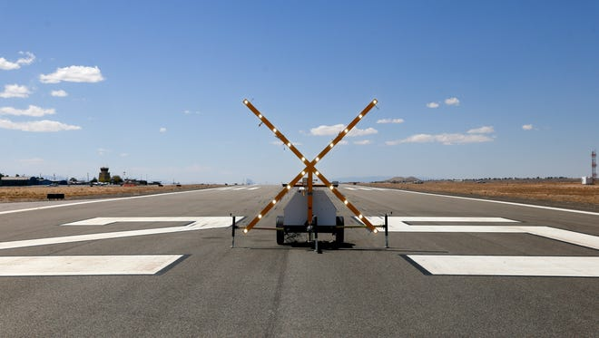 A lighted X closes a runway to traffic as crews put finishing touches on it, Tuesday, April 24 2018 at the Four Corners Regional Airport in Farmington.