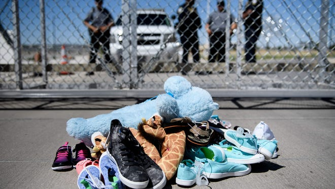 This June 21, 2018, file photo shows security personal standing before shoes and toys left at the Tornillo Port of Entry in Tornillo, Texas, where minors crossing the border without proper papers have been housed after being separated from adults.
