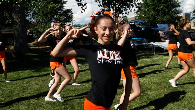 Aztec High School cheerleader Octavia Lovato performers with her team Tuesday during Aztec's National Night Out celebration at Minium Park.