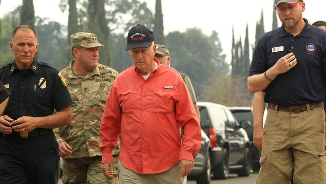 Gov. Jerry Brown, in orange shirt, listens on Saturday, Aug. 4, 2018 as Cal Fire battalion chief, Troy Velin, right, and National Weather Service Meteorologist, Alex Hoon, as they explain how the fire vortex occurred during the Carr Fire.