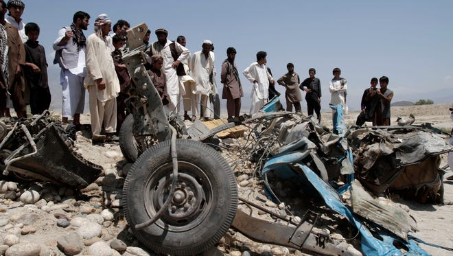 Afghans look at a destroyed vehicle after it was hit by a road side bomb east of Kabul.