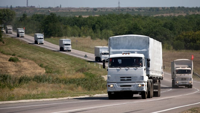 Trucks forming part of an aid convoy destined for Ukraine travel on a road to the border control point in the Russian town of Donetsk, in the Rostov-on-Don region, Russia, Sunday, Aug. 17, 2014. Fighting in Ukraine has escalated since the insurgency arose in April, with government troops steadily taking back rebel-held territory in the east.