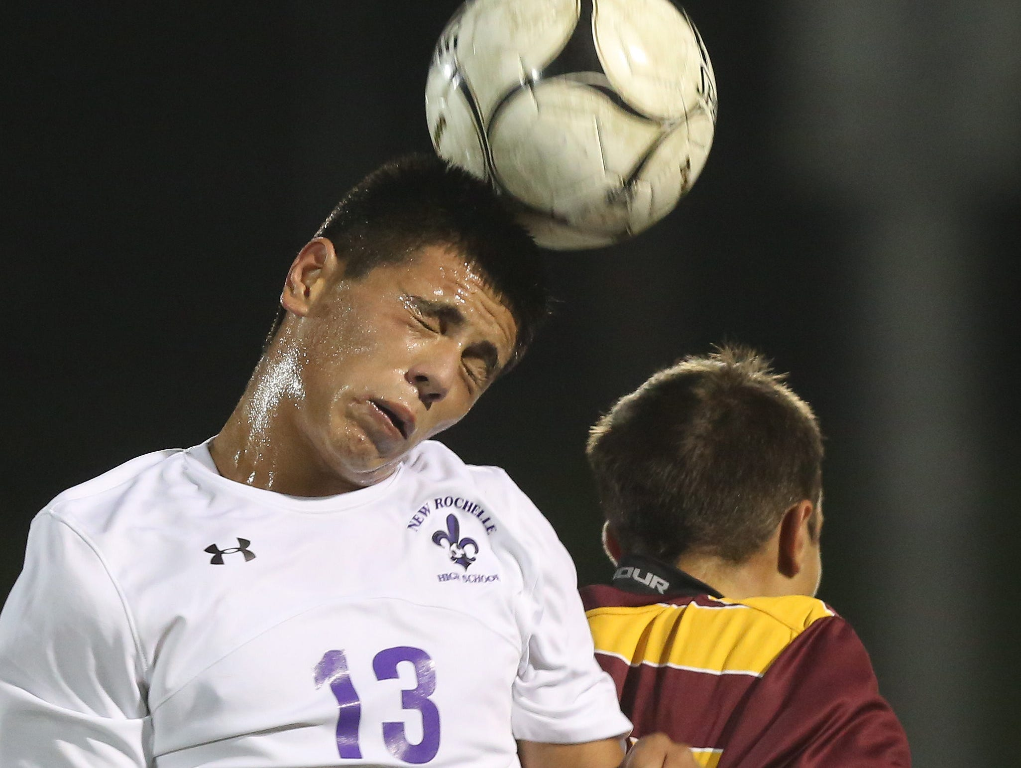 From left, New Rochelle's Oscar Espinoza (13) heads the ball away from an Ithaca defender during the boys soccer regional semifinal at Lakeland High School in Shrub Oak Nov. 2, 2016.