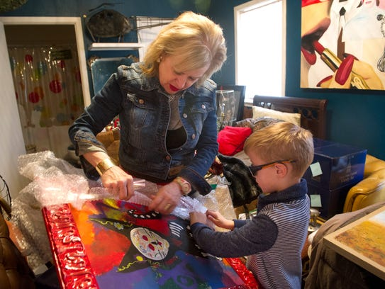 Susan King unpacks some artwork that used to decorate