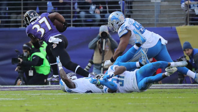 Lions defenders miss Ravens running back Alex Collins, who scored during the first quarter of the Lions' 44-20 loss on Sunday, Dec. 3, 2017, in Baltimore.