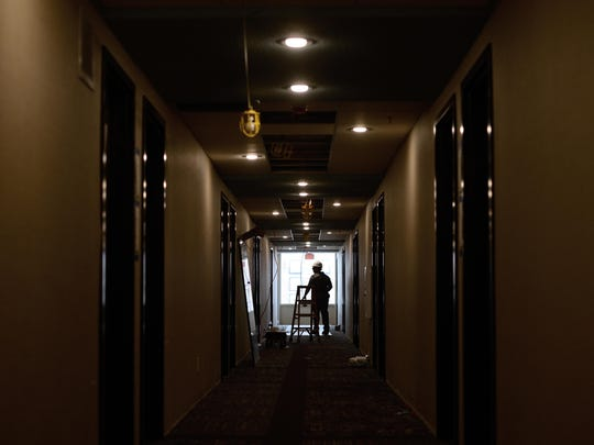 A worker is seen in the hallway of the seventh floor of the Hampton Inn on Main Street in Green Bay.