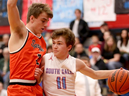 South Salem's Tyler Wadleigh (11) drives through Sprague's Max Long (2) in the first half of the Sprague vs. South Salem boy's basketball game at South Salem High School on Friday, Feb. 3, 2017. Sprague won the game 64-58.