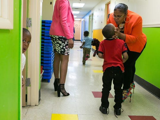 Cora Reed gives a child a kiss as she walks around at Reeds Refuge in Wilmington, an afterschool program for low-income children that also provides arts opportunities.