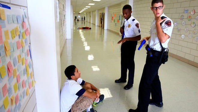 GABE HERNANDEZ/CALLER-TIMES Jacob Mueller (right) and Yordan Journey from Mansfield Explorers Post 1601 talk to an actor portraying a hostage during an active shooter scenario as they compete in the third annual Law Enforcement Explorer Competition on Saturday, Aug. 6, 2016, at Calallen High School in Corpus Christi.