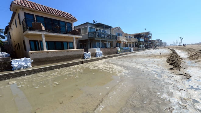 Sandbags are placed in front of some homes in Seal Beach, California on August 27, 2014, where some overnight flooding occurred as the surging ocean water resulting from Hurricane Marie almost reached beachfront homes. California has completed the highest number of goals to prepare for change change, says a 50-state tracker launched Oct. 9, 2014 by the Georgetown Climate Center.