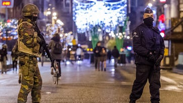 A Belgian Army soldier and policeman patrol on a main boulevard in Brussels on Sunday.