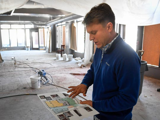 "Casey Todd looks over a schematic of the new restaurant ""Hometown Roots"" last year before it opened in August. Todd's restaurant was one of two Small Business of the Year winners at Thursday evening's Kyndle annual dinner."