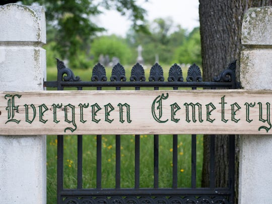The entrance to Evergreen Cemetery in Camden.  The cemetery is overgrown and littered with trash and debris.