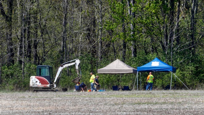 Authorities work along a rural wooded area in Macomb Township, Mich., Tuesday, May 8, 2018. Authorities excavating woods in southeastern Michigan, about 30 miles from downtown Detroit, for the remains of a 12-year-old girl last seen in 1979, also could be looking for the bodies of up to half a dozen others who have been reported missing over the years. The search started Monday for the remains of Kimberly King, but Warren Police Commissioner Bill Dwyer said there could be others buried in the area.