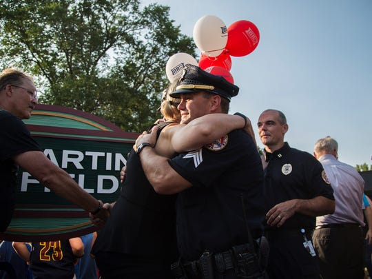 Jayne Martin, mother of Urbandale Police Officer Justin Martin who was killed while on duty last fall, hugs a  member of the Urbandale Police Department after cutting the ribbon on the Martin Soccer Fields dedicated in Martin's honor during the ninth annual Urbandale National Night Out on Tuesday, Aug 1, 2017, outside the Urbandale Police Department.
