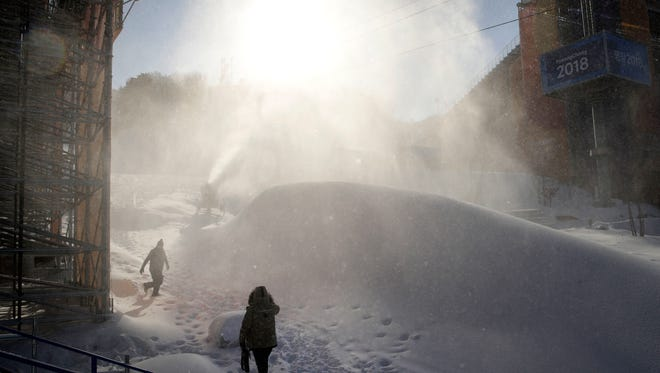 Workers pass a snow-making machine at Phoenix Snow Park in Pyeongchang on Feb. 3.