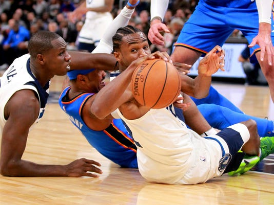 Minnesota Timberwolves guard Andrew Wiggins (22) passes from the floor as Oklahoma City Thunder forward Carmelo Anthony defends, while Timberwolves' Gorgui Dieng (5) reaches out during the first quarter of an NBA basketball game Wednesday, Jan. 10, 2018, in Minneapolis. (AP Photo/Andy Clayton-King)