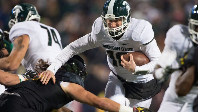 MSU quarterback Connor Cook (18) runs past Maryland's Darius Kilgo (97) during the first quarter of the Spartans' 37-15 win on Nov. 15, 2014, in College Park, Md.