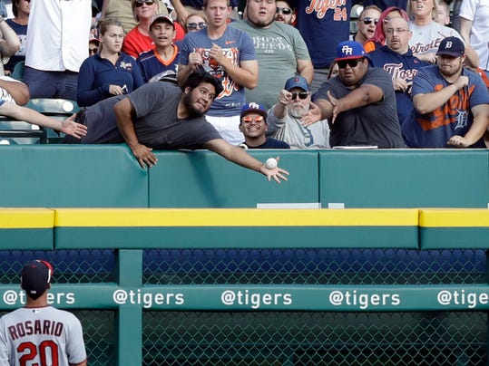 A baseball fan reaches for the grand slam hit by Detroit Tigers' James McCann during the first inning of a baseball game against the Minnesota Twins, Saturday, Aug. 12, 2017, in Detroit. (AP Photo/Carlos Osorio)