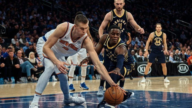 New York Knicks' Kristaps Porzingis, left, competes for the ball with Indiana Pacers' Darren Collison, centre, during the first half of a NBA basketball game at Madison Square Garden in New York, Sunday, Nov. 5, 2017.