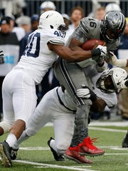 Ohio State quarterback J.T. Barrett, top right, is sacked by Penn State defenders Jason Cabinda, left, and Manny Bowen during the first half of an NCAA college football game Saturday, Oct. 28, 2017, in Columbus, Ohio. (AP Photo/Jay LaPrete)