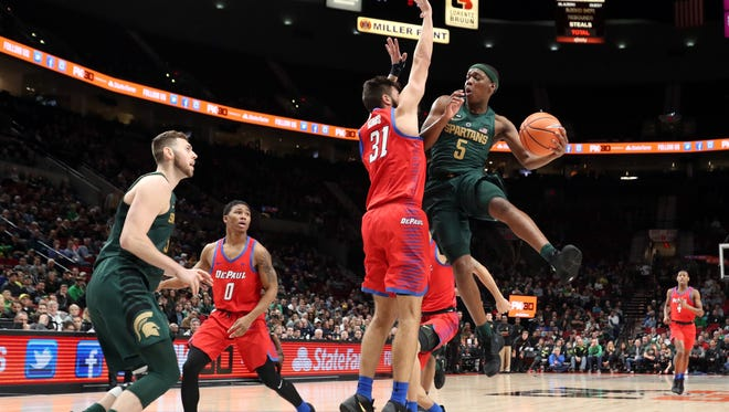 Michigan State's Cassius Winston wraps around a pass to teammate Ben Carter during the first half of MSU's 73-51 win over DePaul Thursday night.