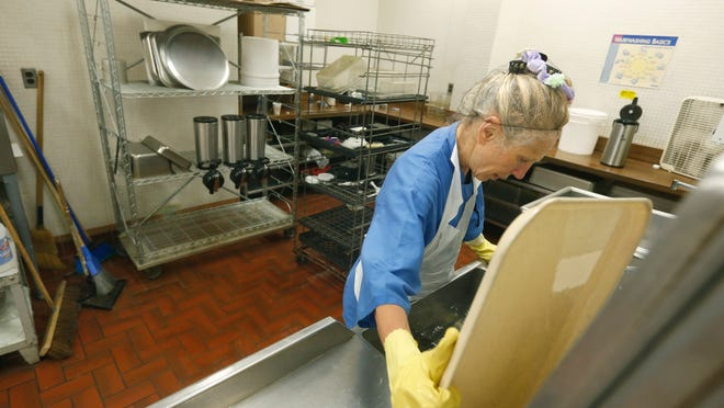 Sherryl Freeman of Brighton washes dishes in the kitchen at Brighton High School. Voters in the district will consider a proposition to approve $1.4 million for capital improvements.