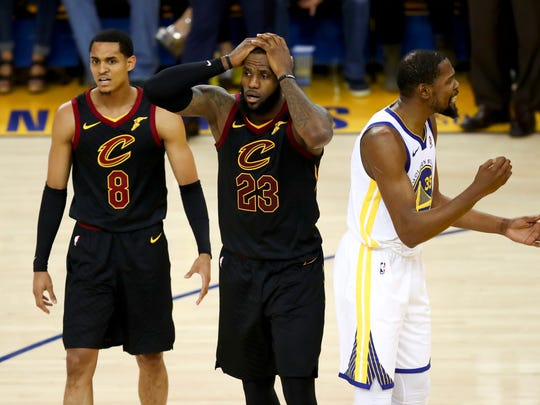 Cleveland Cavaliers forward LeBron James (23) reacts between guard Jordan Clarkson (8) and Golden State Warriors forward Kevin Durant during the second half of Game 1 of basketball's NBA Finals in Oakland, Calif., Thursday, May 31, 2018. (AP Photo/Ben Margot)