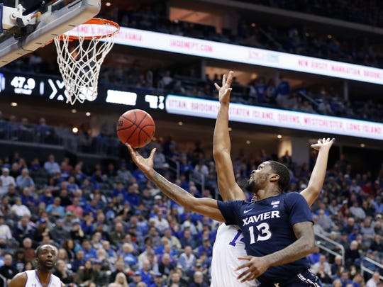 Xavier's Naji Marshall (13) attempts a layup as Seton Hall's Jared Rhoden (14) defends during the first half of an NCAA college basketball game, Saturday, feb. 1, 2020, in Newark, N.J. (AP Photo/Michael Owens)