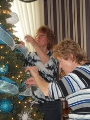 Donna Ney and Mindy Peters decorate their tree at Vilas